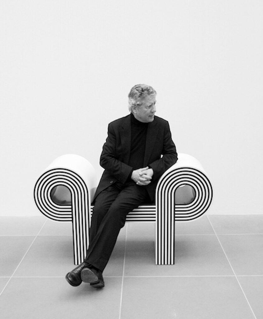 Ritratto in bianco e nero di Marcello Morandini seduto su una sua opera.
